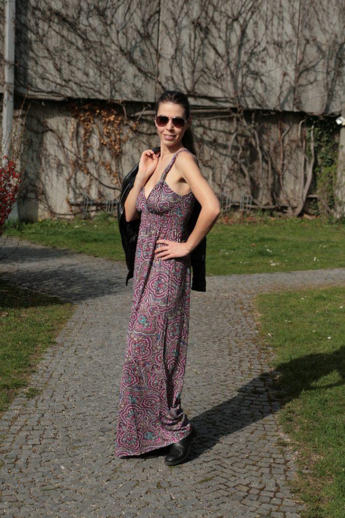 Frau trägt Maxikleid im Hippie-Look zur Lederjacke