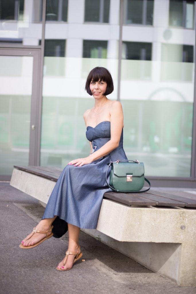 Frau im Outfit mit Jeanskleid und grüner Tasche