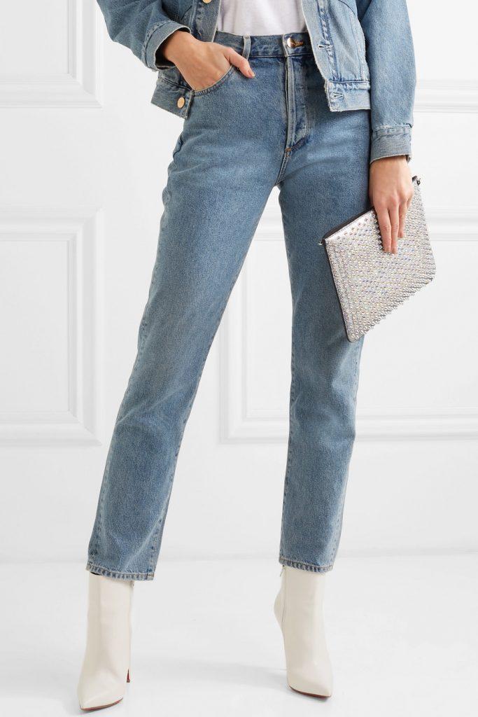 High Waist Jeans in blue denim mit silberner Clutch und weißen Stiefeletten