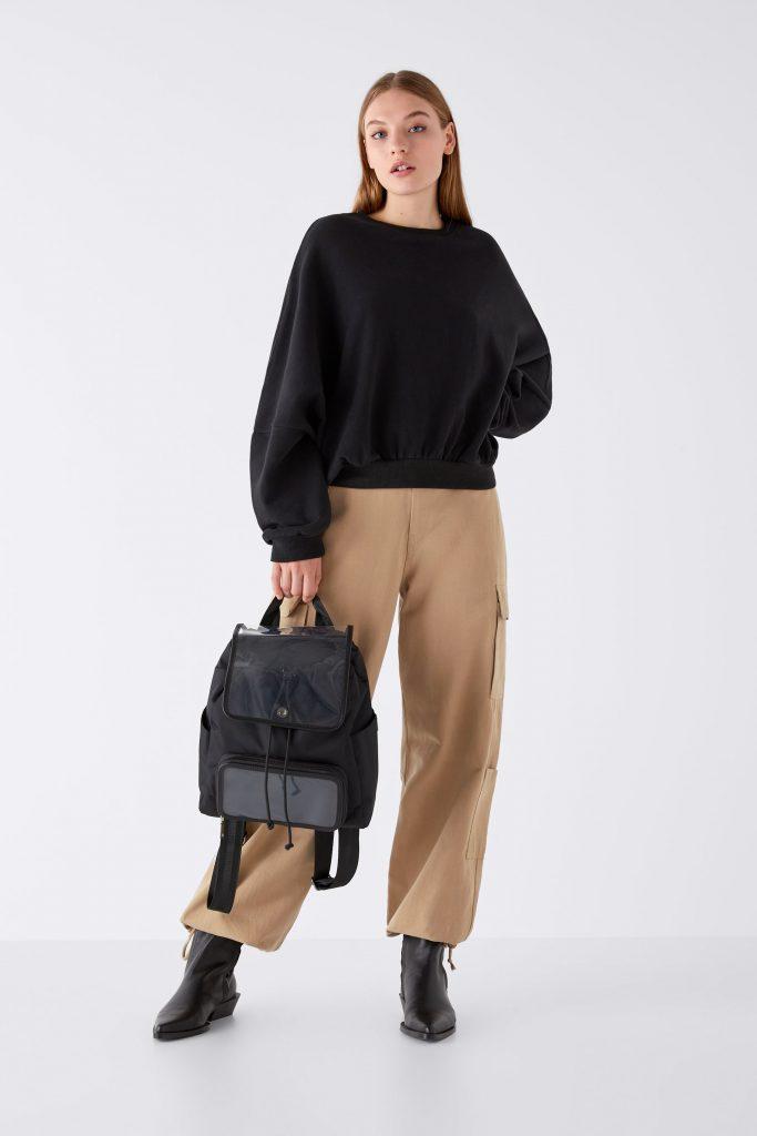 Oversized Pullover in schwarz mit beiger Hose und Rucksack