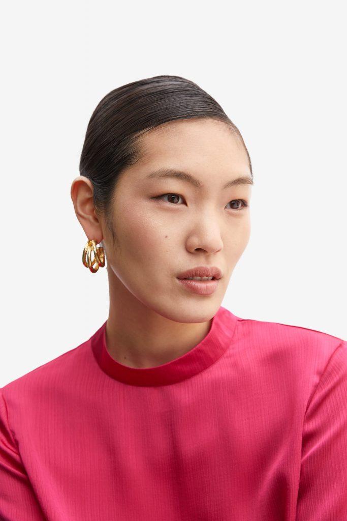 Frau mit großen Statementorringen und pinkfarbener Bluse