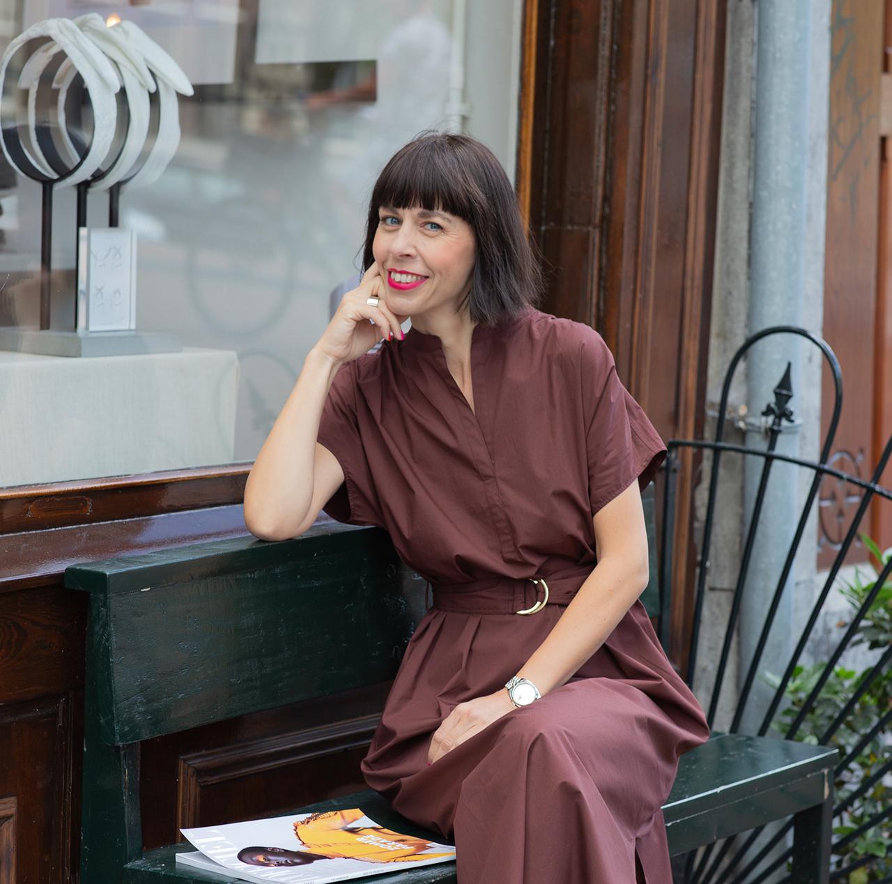 Frau sitzt an einer Boutique - Trendfarbe braun kombinieren