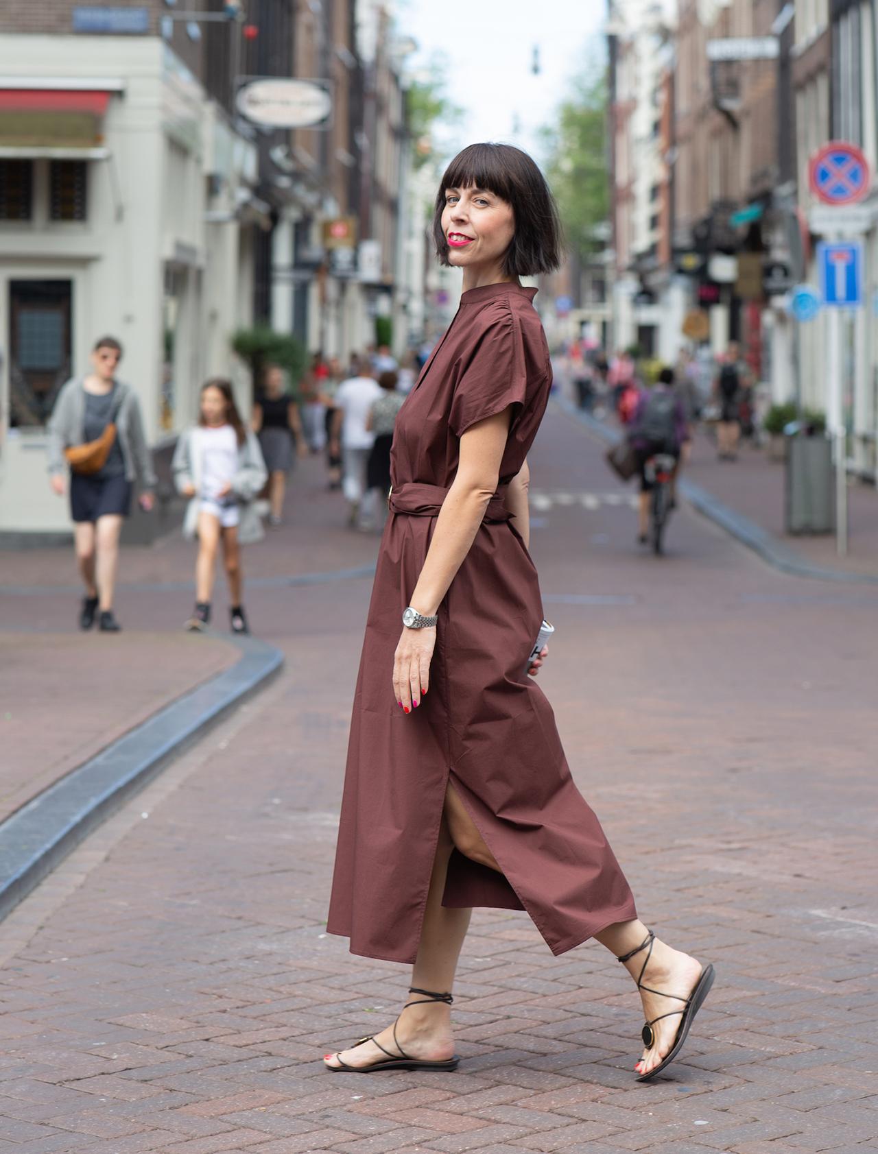 Frau läuft die Straße entlang mit bodenlangem Kleid - Trendfarbe Braun kombinieren