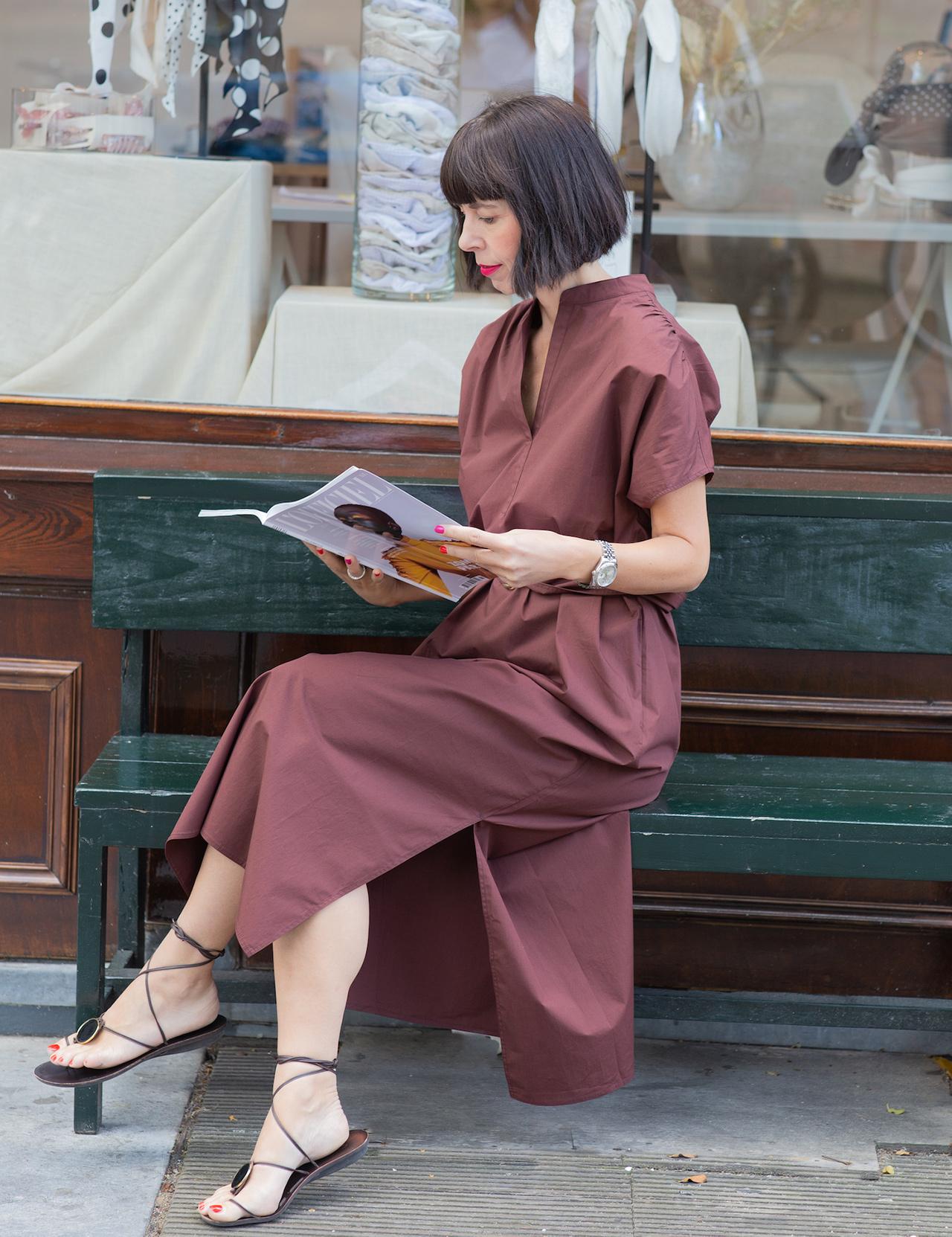 Trendfarbe Braun kombinieren - Frau sitzend auf einer Bank mit einer Zeitschrift in der Hand