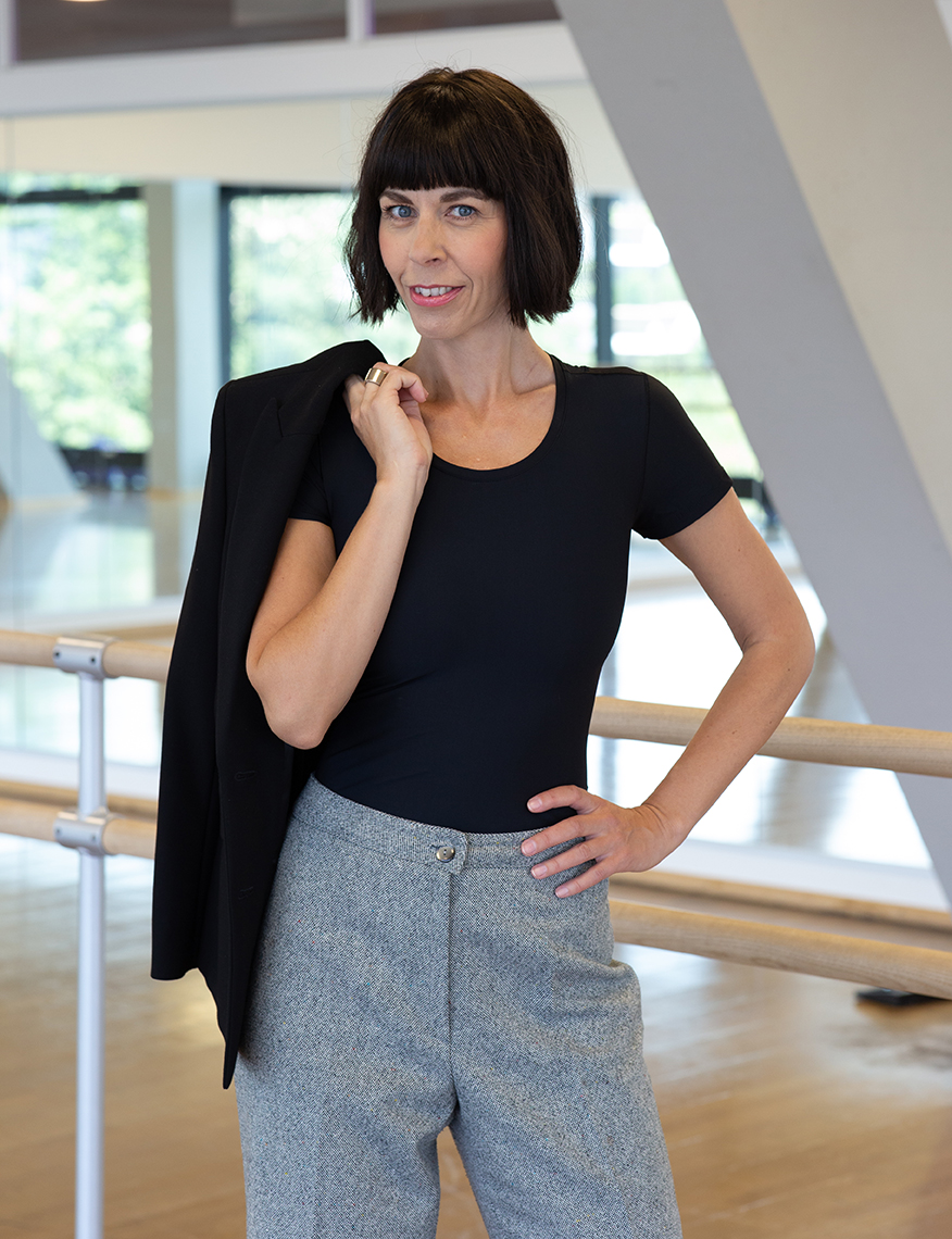 Frau mit schwarzen Haaren und T-Shirt - Warum Shapewear deine Haltung und Ausstrahlung pusht