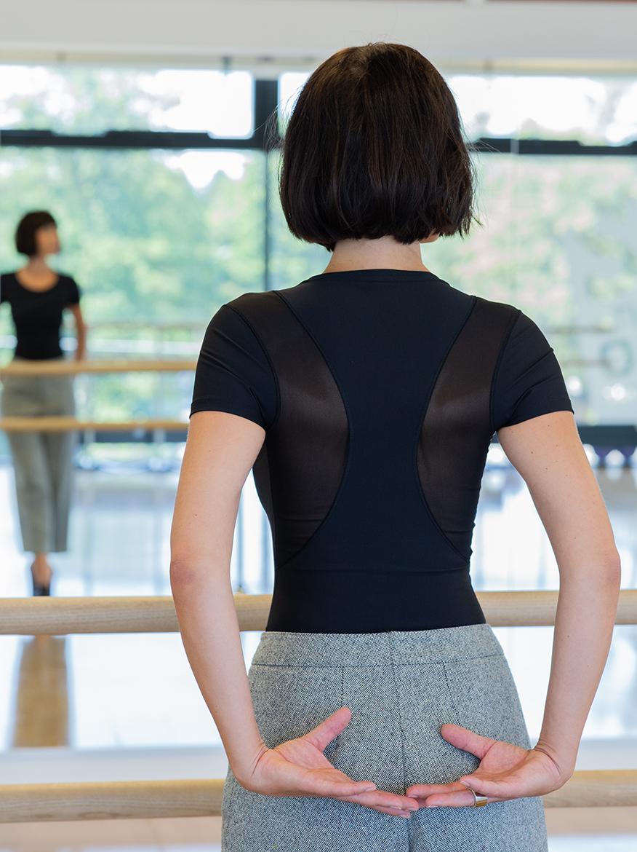 Frau mit Longbob und schwarzen T-Shirt vor einem Spiegel - Warum Shapewear deine Haltung pusht