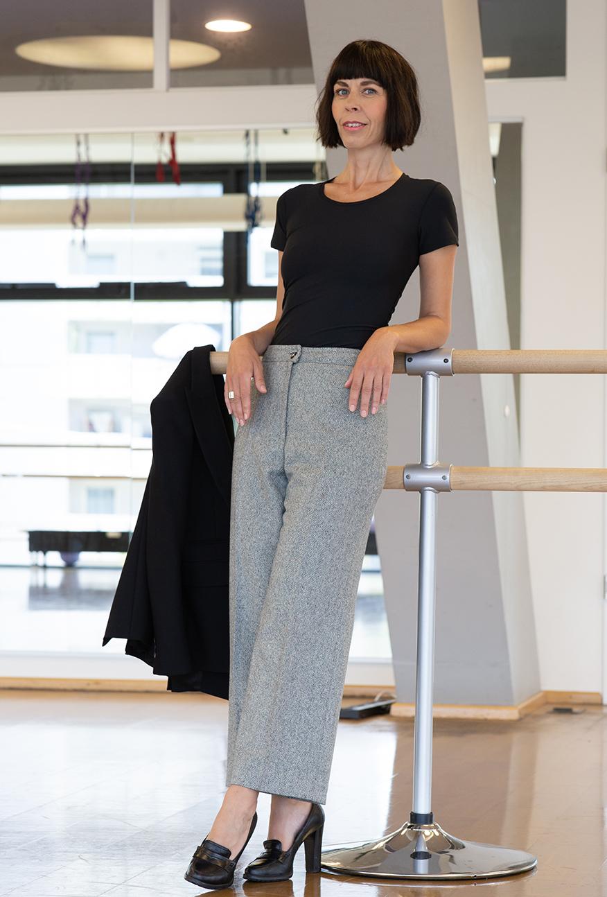 Frau im schwarzen T-Shirt an einer Ballettstange - Shapewear pusht deine Ausstrahlung und Haltung