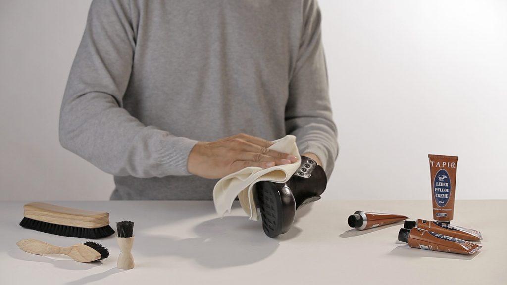 Mann poliert einen schwarzen Schuh