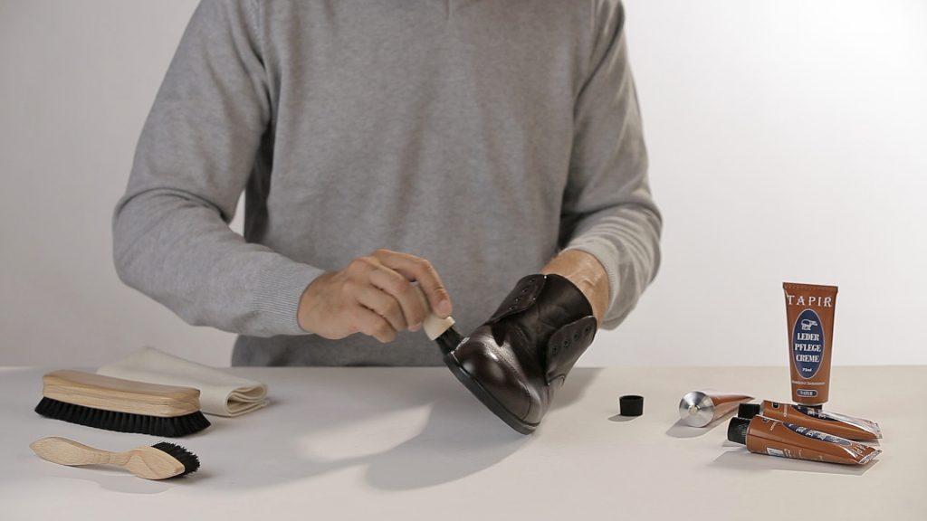 Mann putz einen schwarzen Schuh mit Lederpflege