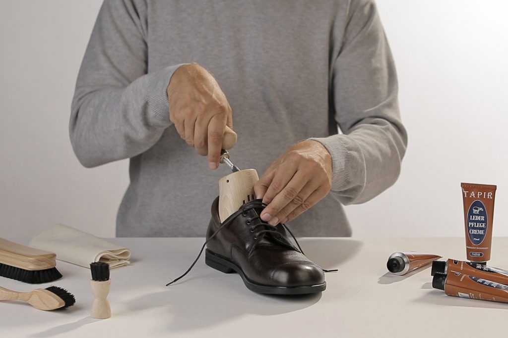 Mann legt in seinen schwarzen Schuh einen Schuhspanner ein
