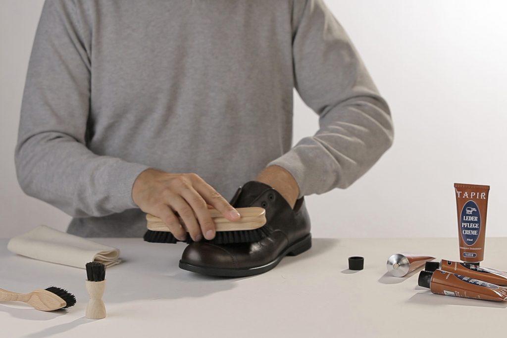 Mann bürstet schwarze Schuhe