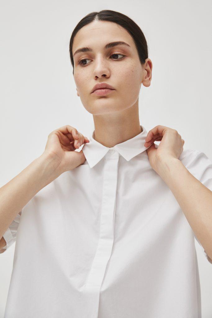 Frau mit dunkelbraunen Haaren zum Zopf gebunden mit weißer Bluse greift sich an den Kragen