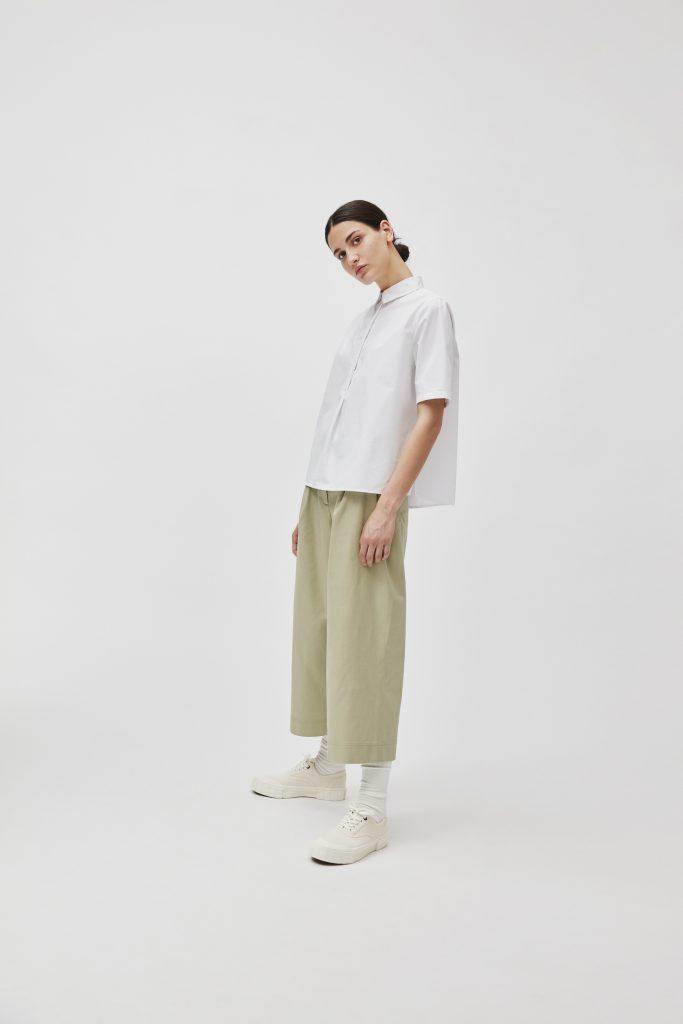 Frau mit schwarzen Haaren und weißer Bluse mit Culotte weißen Strümpfen und weißen Sneakern