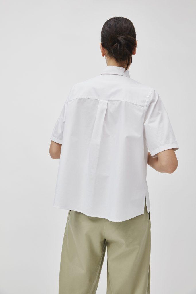 Frau mit weißer Bluse und cremefarbener Hose