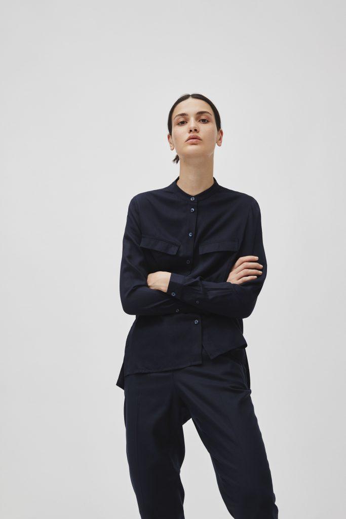 Schlanke Frau mit schwarzem Haar und dunkelblauer Bluse und Hose