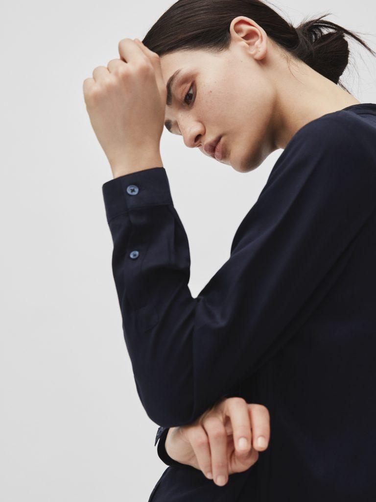 Frau mit schwarzem Dut und dunkelblauer Bluse