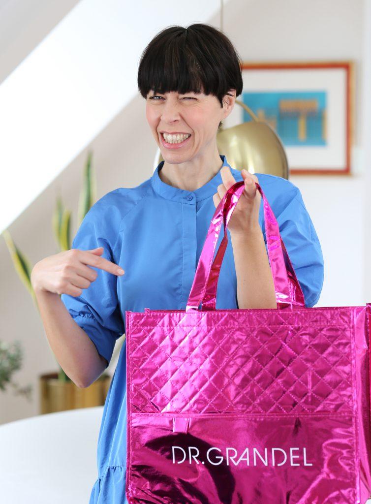Eine Frau mit schwarzen Haaren steht angelehnt an einem Tisch mit einer Shopping Bag in der Hand von Dr. Grandel