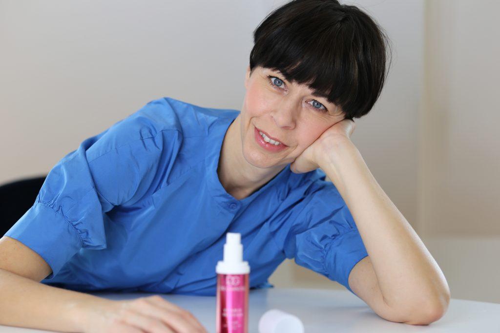 Frau mit schwarzem kurzen Haarschnitt lehnt an einem weißen Tisch mit einem Serum von dr. Grandel vor sich