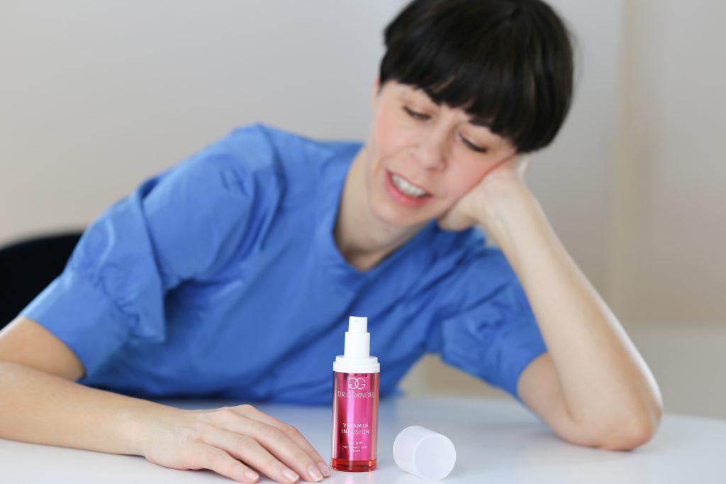 ein Serum steht auf einem weißen Tisch vor einer Frau mit schwarzem Haar und blauen Kleid