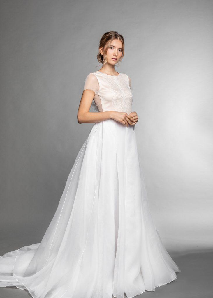 Ein bodenlanges weißes Brautkleid mit Ärmelansatz bei einer Frau mit blondem Haar