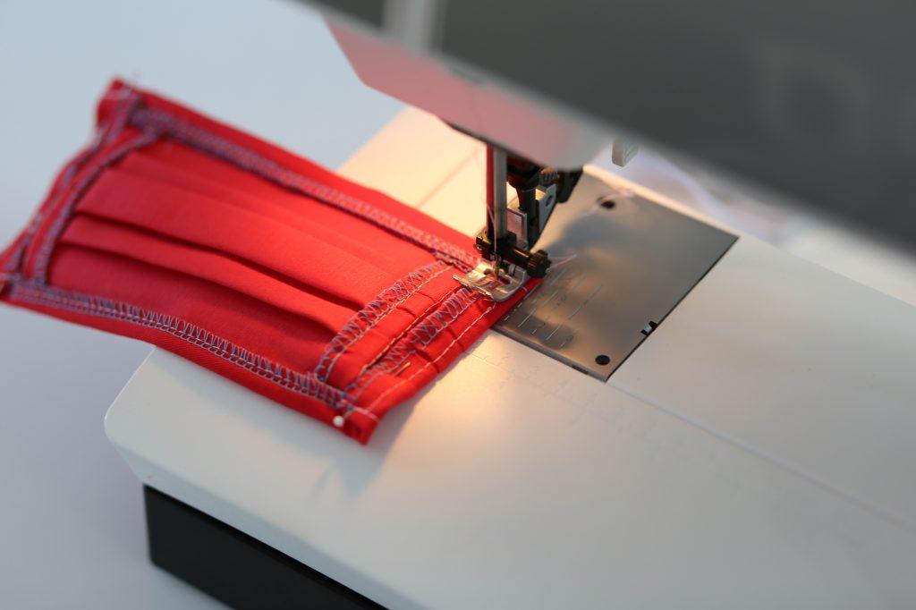 Zwei Stoffteile werden an der Nähmaschine zusammengenäht