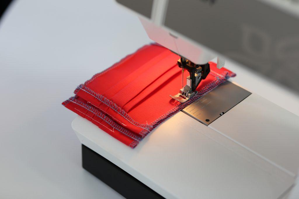rotes Stoffteil für die Maske unter der Nähmaschine