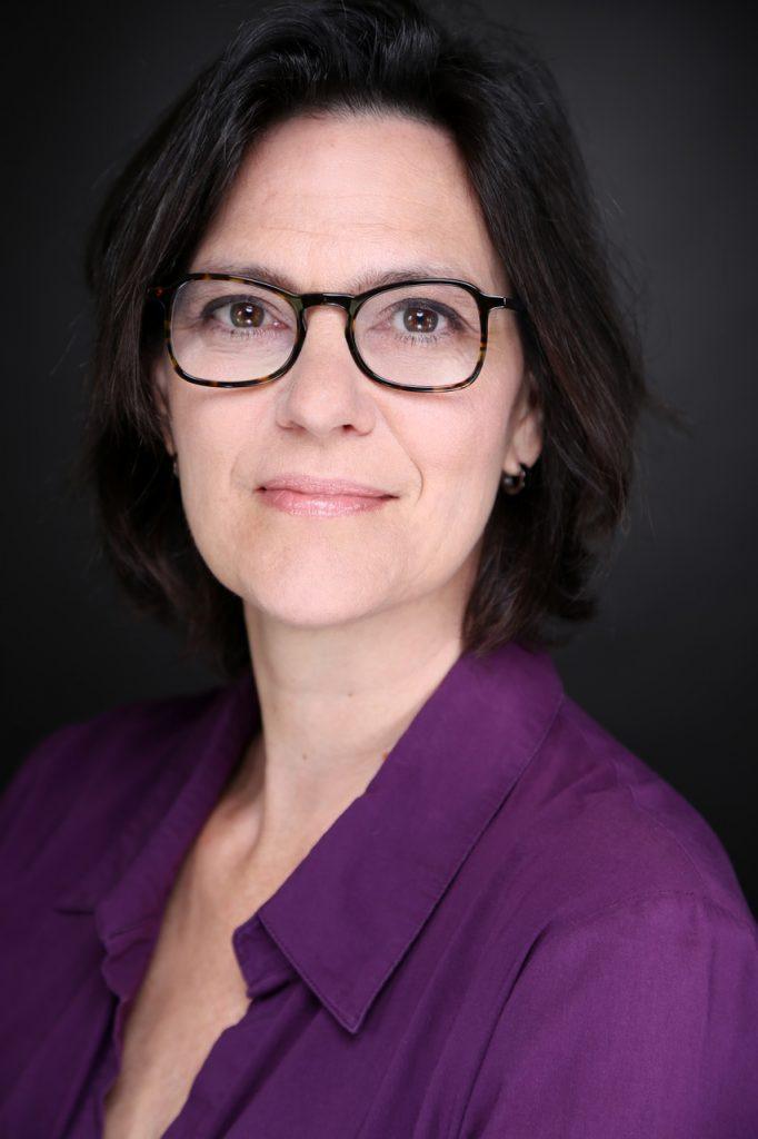 Eine Frau mit schwarzem Haar und lila farbener Bluse