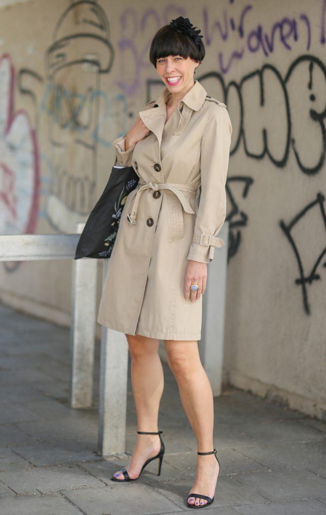 Frau mit kurzem dunklen Haar mit einem Trenchcoat