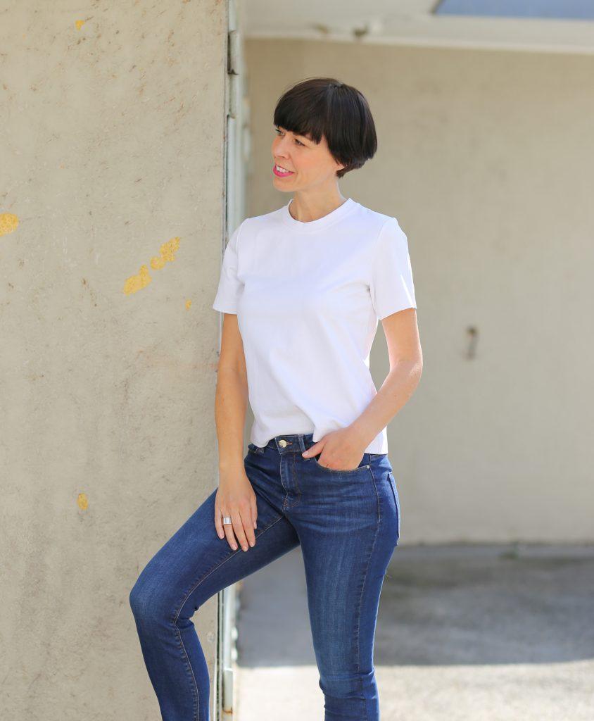 Frau mit kurzem schwarzem Haar trägt ein weisses T-Shirt und Skinny Hosen und lächelt