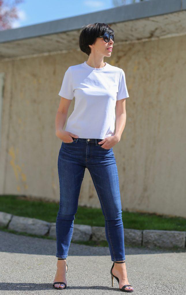 Frau mit kurzem schwarzem Haar und schwarzer Sonnenbrille trägt ein weisses T-Shirt und Skinny Hosen