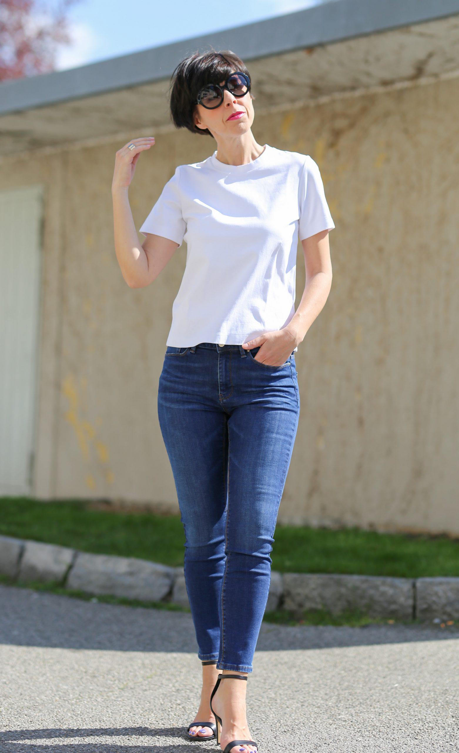 Frau mit kurzem schwarzem Haar und schwarzer Sonnenbrille trägt ein weisses T-Shirt und Skinny Hosen und High Heels