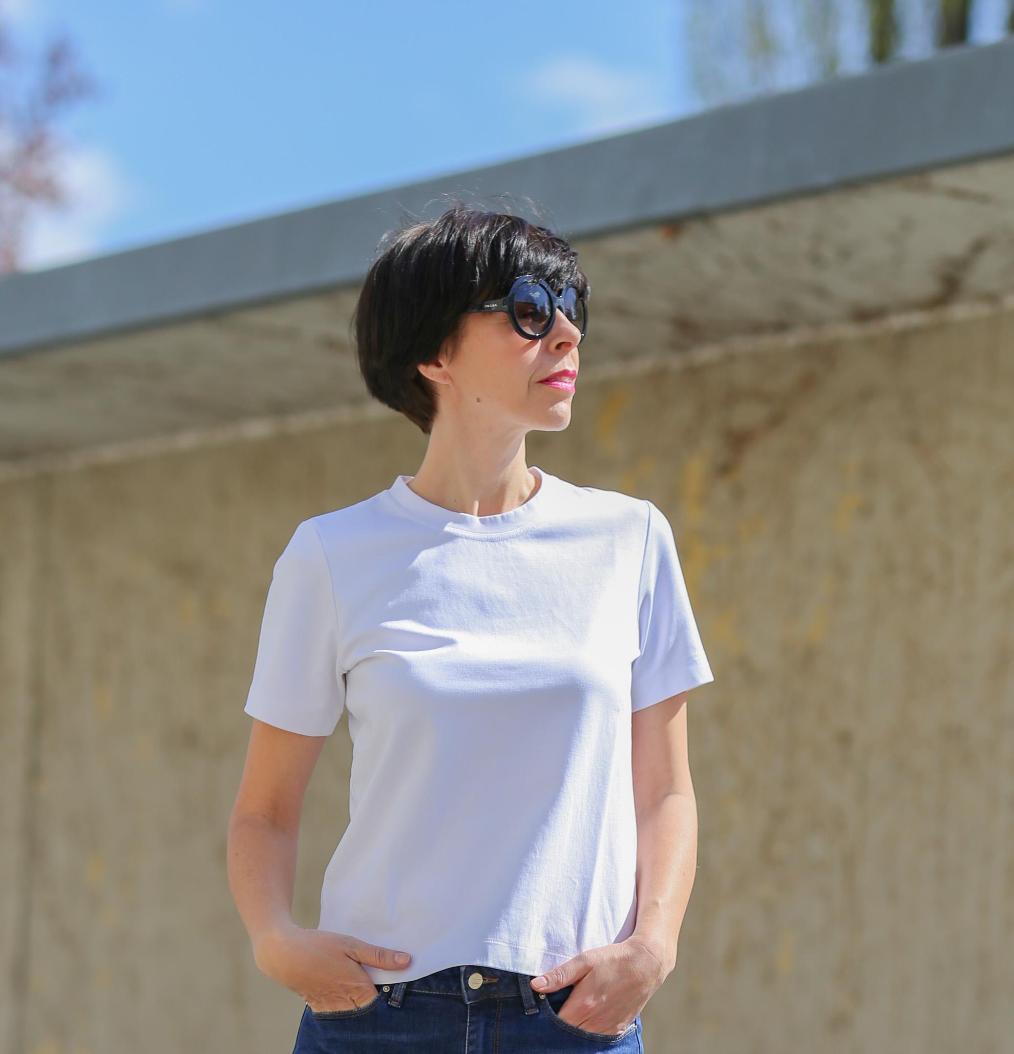 Frau mit kurzem schwarzem Haar und schwarzer Sonnenbrille trägt ein weisses T-Shirt und schaut zur Sonne