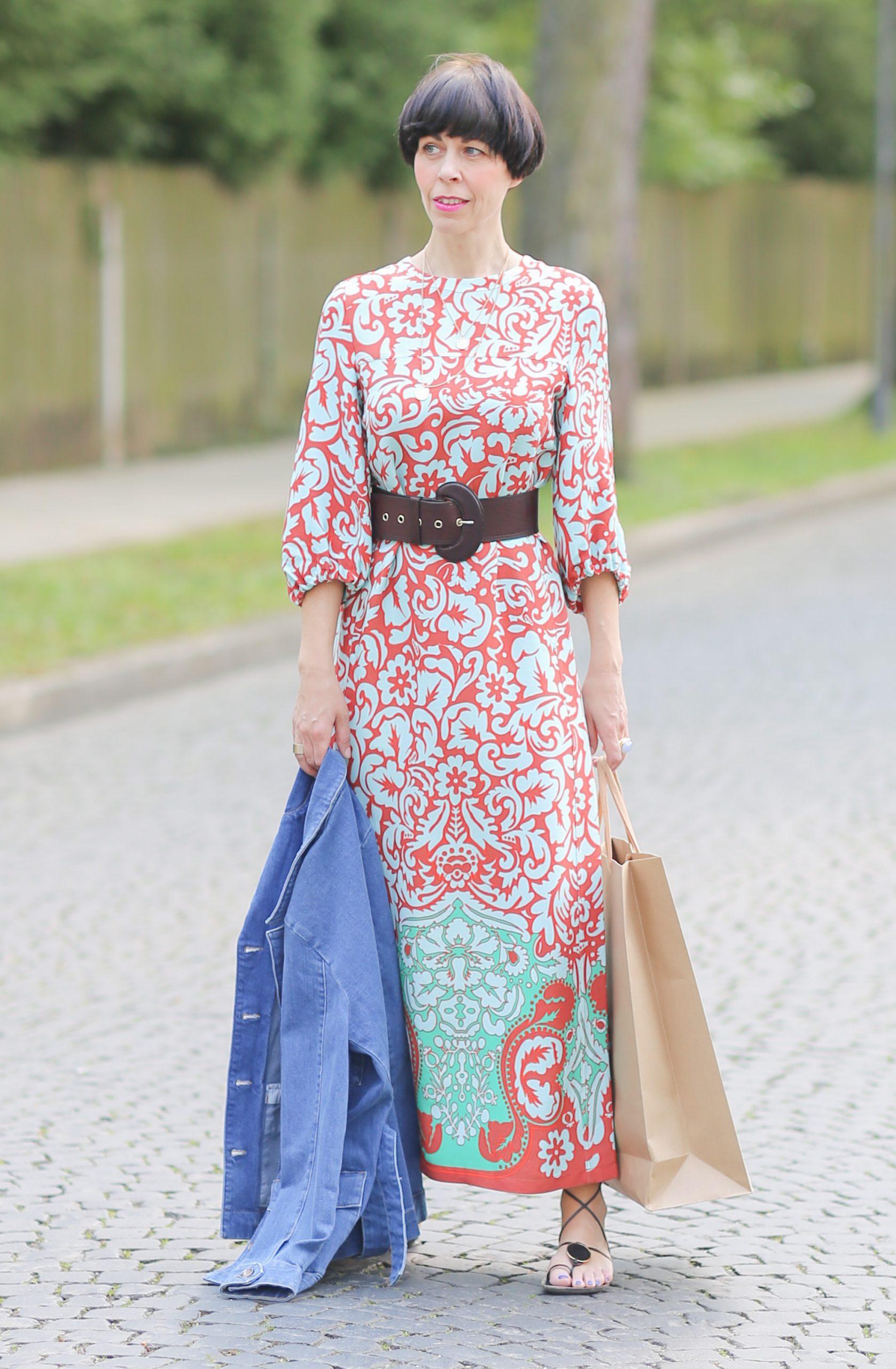 Städtetrip Eine Frau mit einem bunten Maxikleid steht auf der Straße mit einer Jeansjacke in ihrer Hand und ihrer Shoppingbag