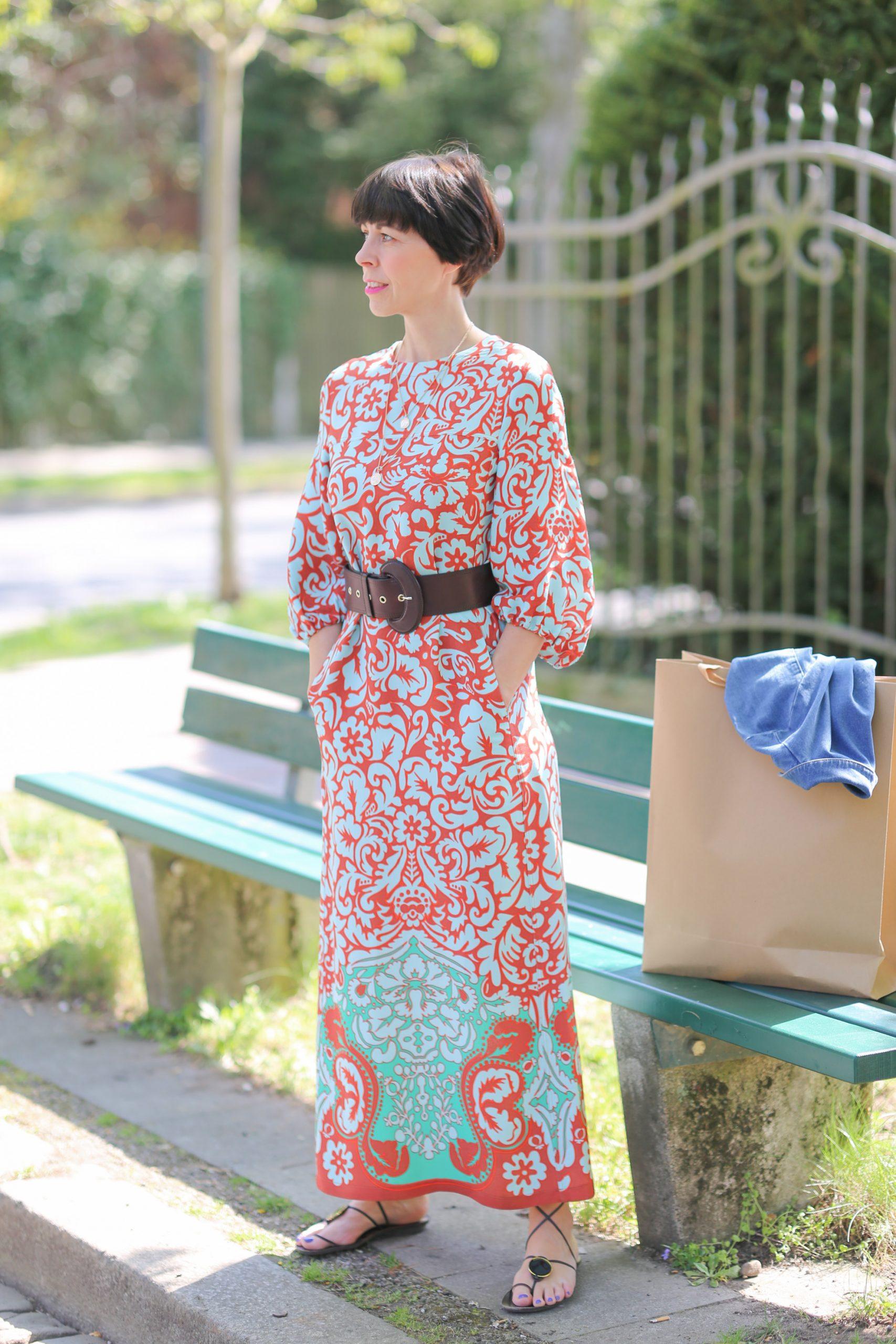 Städtetrip Eine Frau mit einem bunten Maxikleid wartet an einer Bank mit ihrer Shoppingbag
