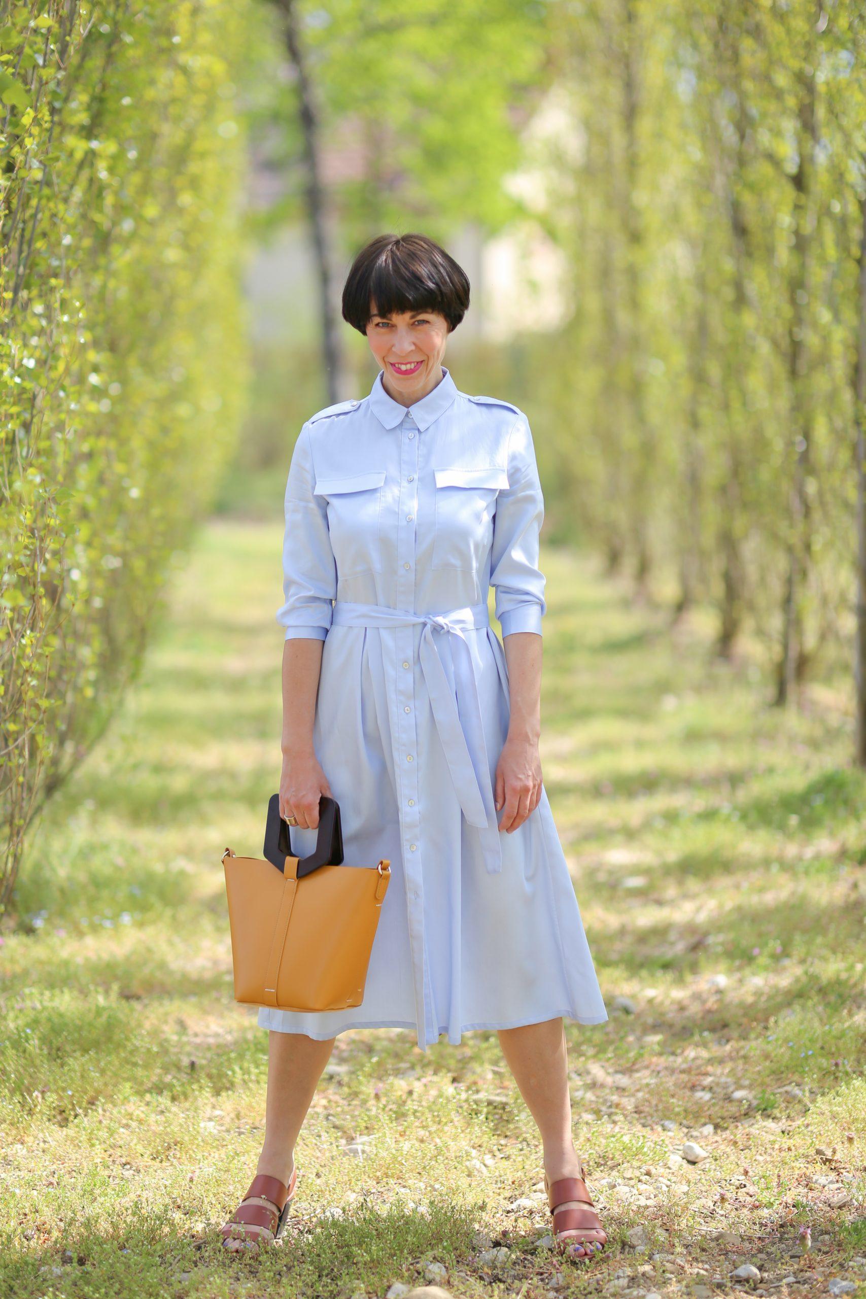 Frau mit kurzem schwarzen Haar trägt eine Skinny Jeans und ein Hemdblusenkleid von Nina Rein Fashion