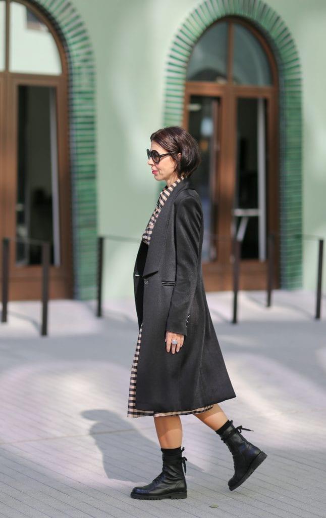 Frau mit schwarzem Haar und einem karierten Kleid mit einem schwarzen Longblazer und Schnürstiefel und Sonnenbrille läuft auf dem Fussweg