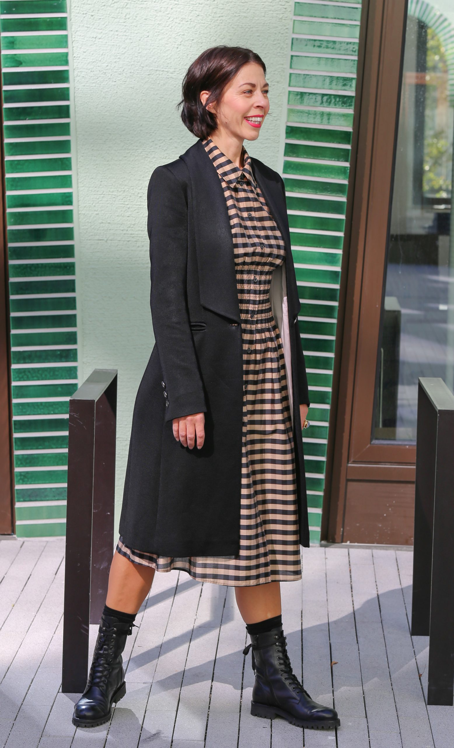 Ausbildung zur Farb- und Stilberaterin Frau mit schwarzem Haar und einem karierten Kleid mit einem schwarzen Longblazer und Schnürstiefel und Sonnenbrille läuft auf dem Fussweg