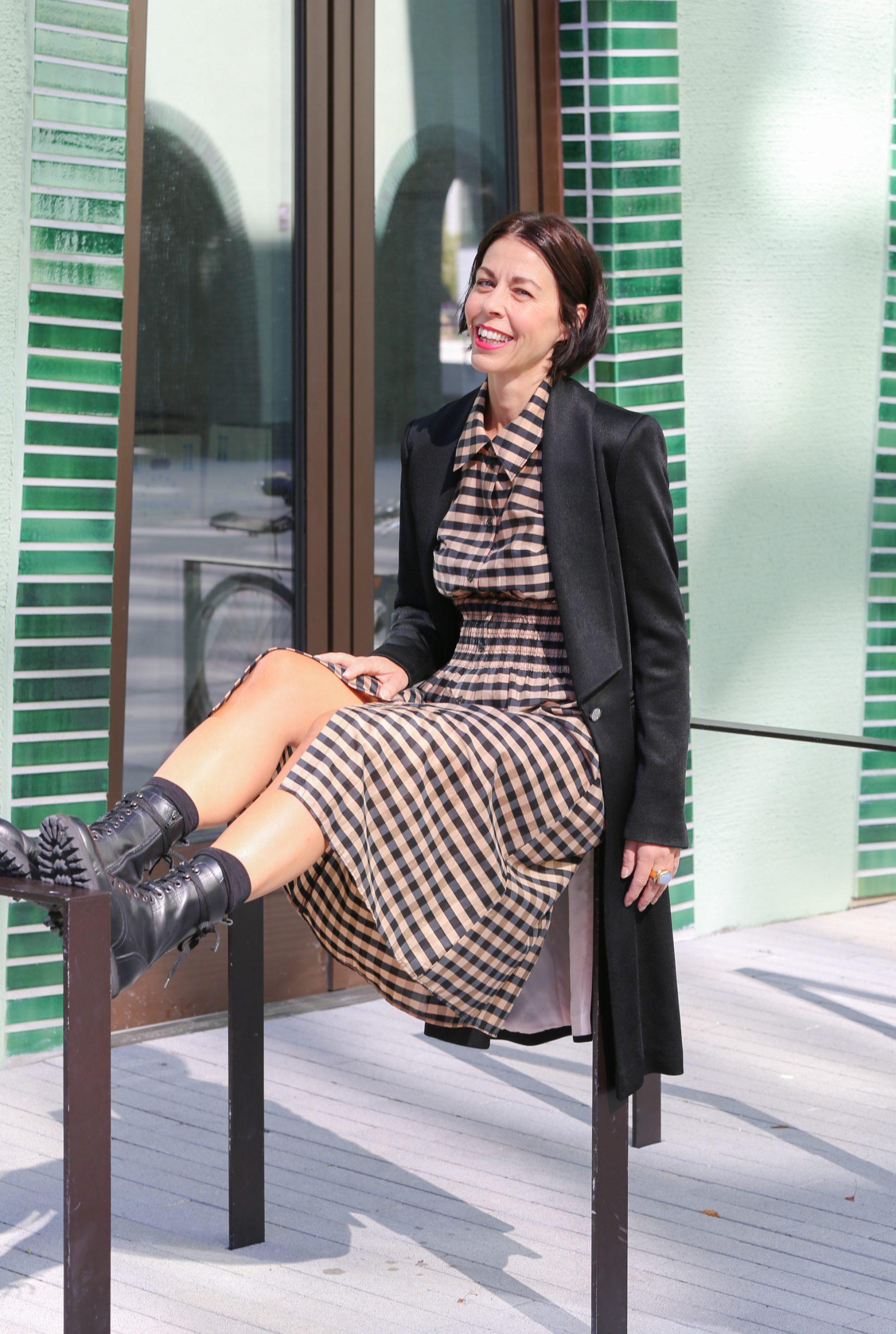 Modetrends Herbs/Winter 2020/21 Frau mit schwarzem Haar und einem karierten Kleid mit einem schwarzen Longblazer und Schnürstiefel und Sonnenbrille läuft auf dem Fussweg