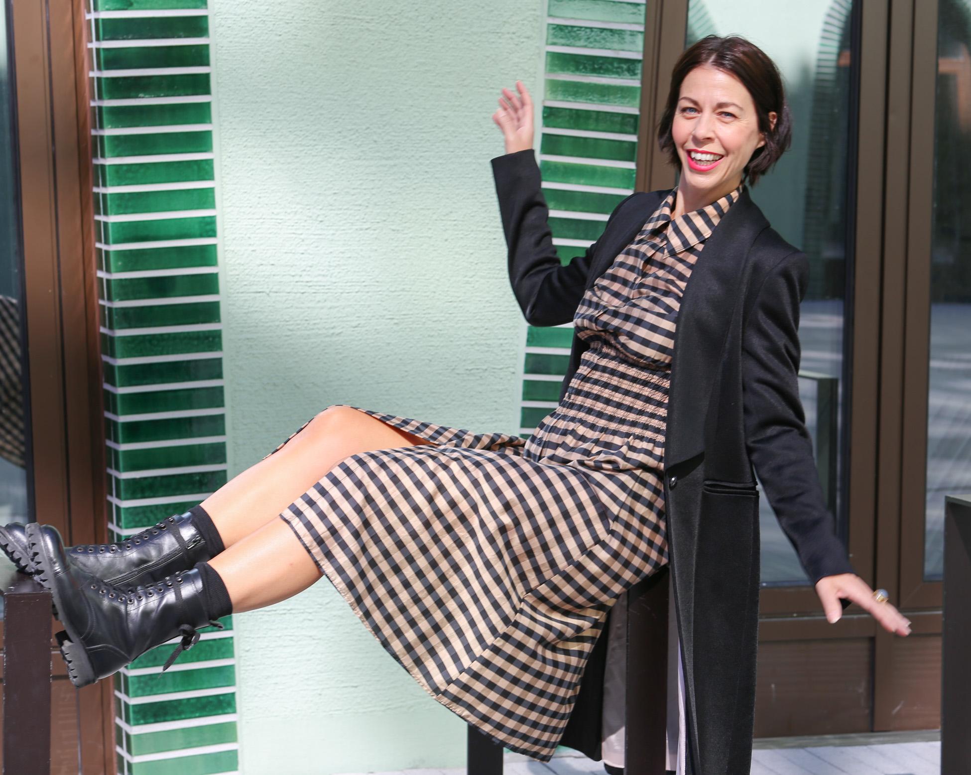Frau mit schwarzem Haar und einem karierten Kleid mit einem schwarzen Longblazer und Schnürstiefel sitzt auf einem Geländer