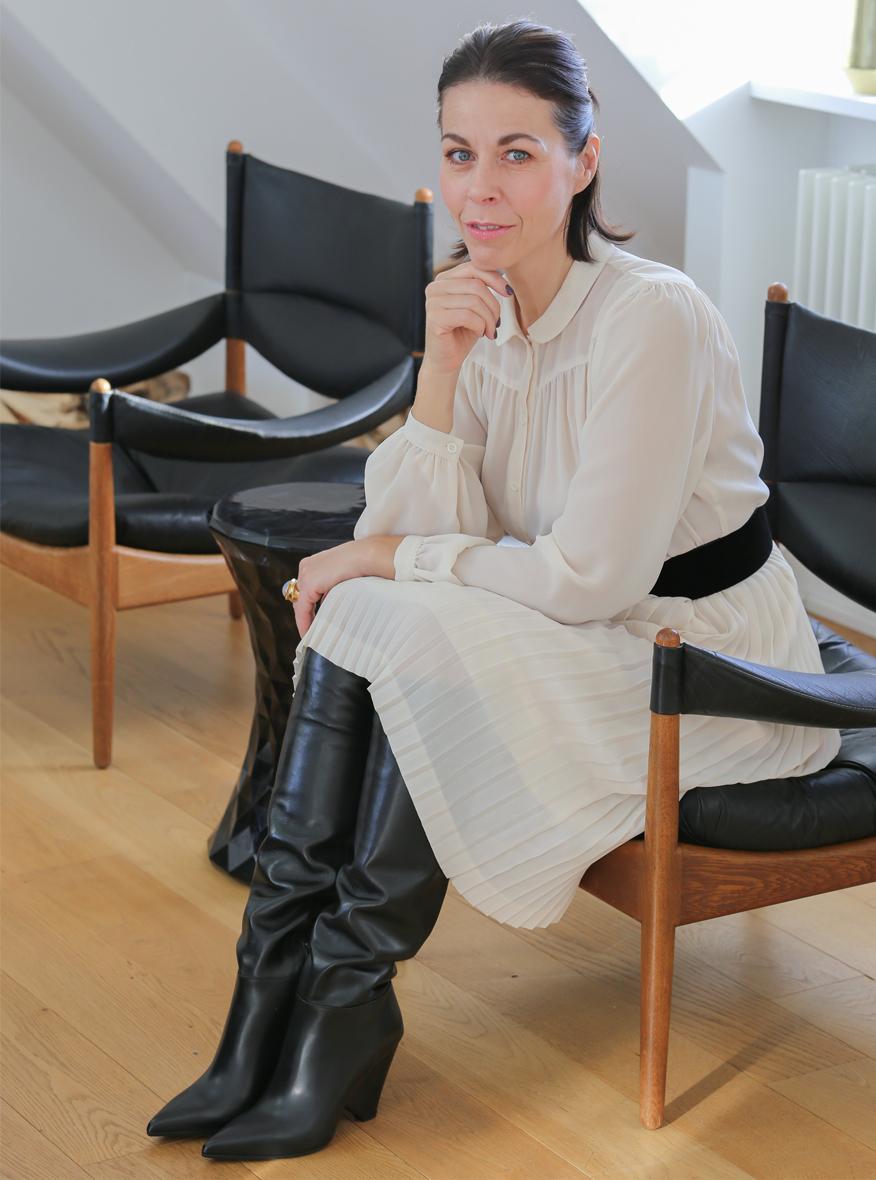 Ausbildung zur Farb- und Stilberaterin Frau mit halblangen dunklen Haar mit einem beigen Kleid auf schwarzen Lederstühlen sitzend