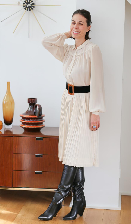 Second Hand Frau mit halblangen dunklen Haar mit einem beigen Kleid steht an einer weißen Wand