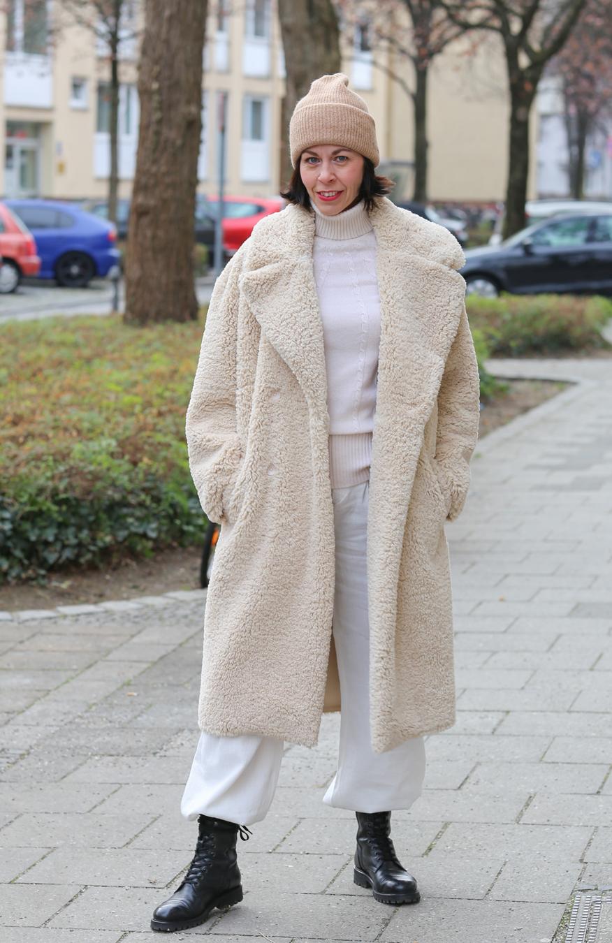Der Teddy-Mantel Frau mit dunklem Haar und eine Mütze in beige, einem off white farbenen Kashmir Pullover und einem off white farbenen Teddy Mantel