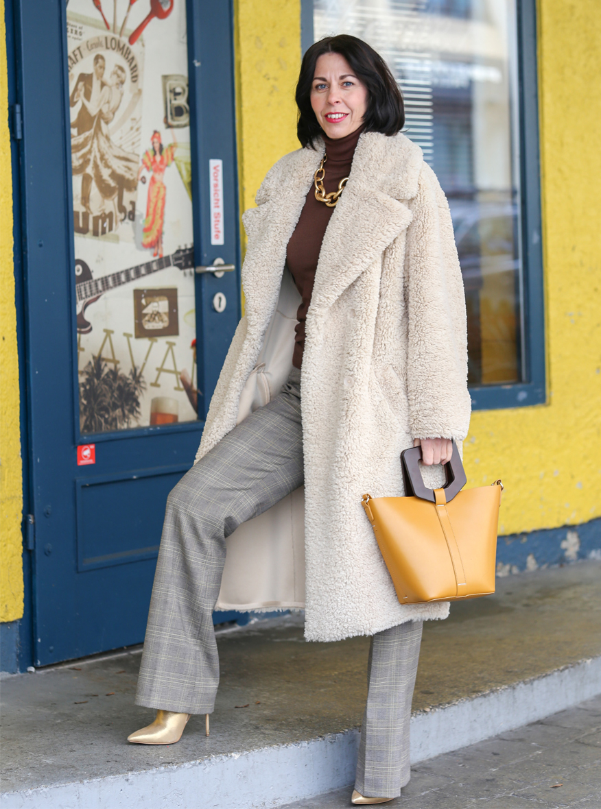 Der Teddy-Mantel Eine Frau mit dunklem Haar einer karierten Marlene Hose, braunen Rolli und einem off white Teddy Mantel steht auf dem Gehweg