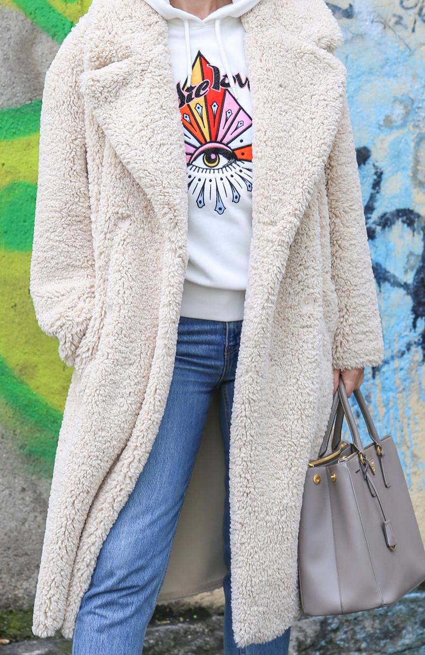 Der Teddy-Mantel Eine Frau mit hellem Hoodie und Mom Jeans und einem Teddy Mantel in off white