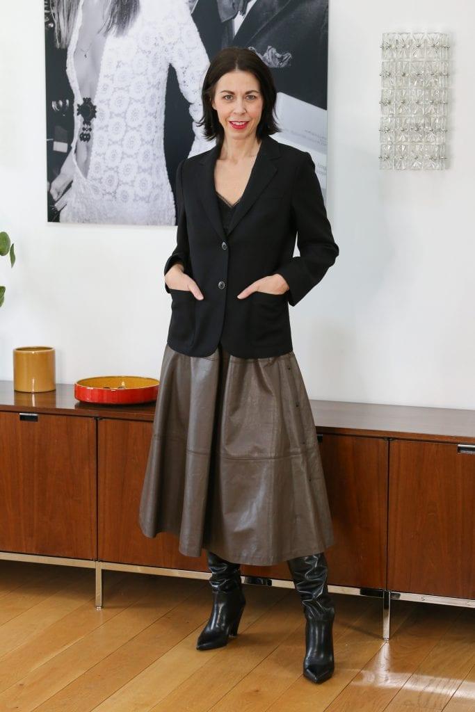 Eine Frau mit halblangen dunklen Haaren hat einen schwarzen Blazer und einen braunen Rock an und dazu schwarze Stiefel