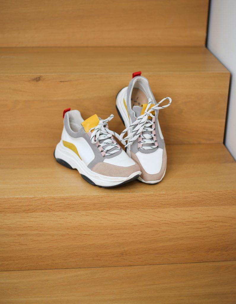 Ein Produktfoto mit nachhaltigen weißen Sneakern mit bunten Details