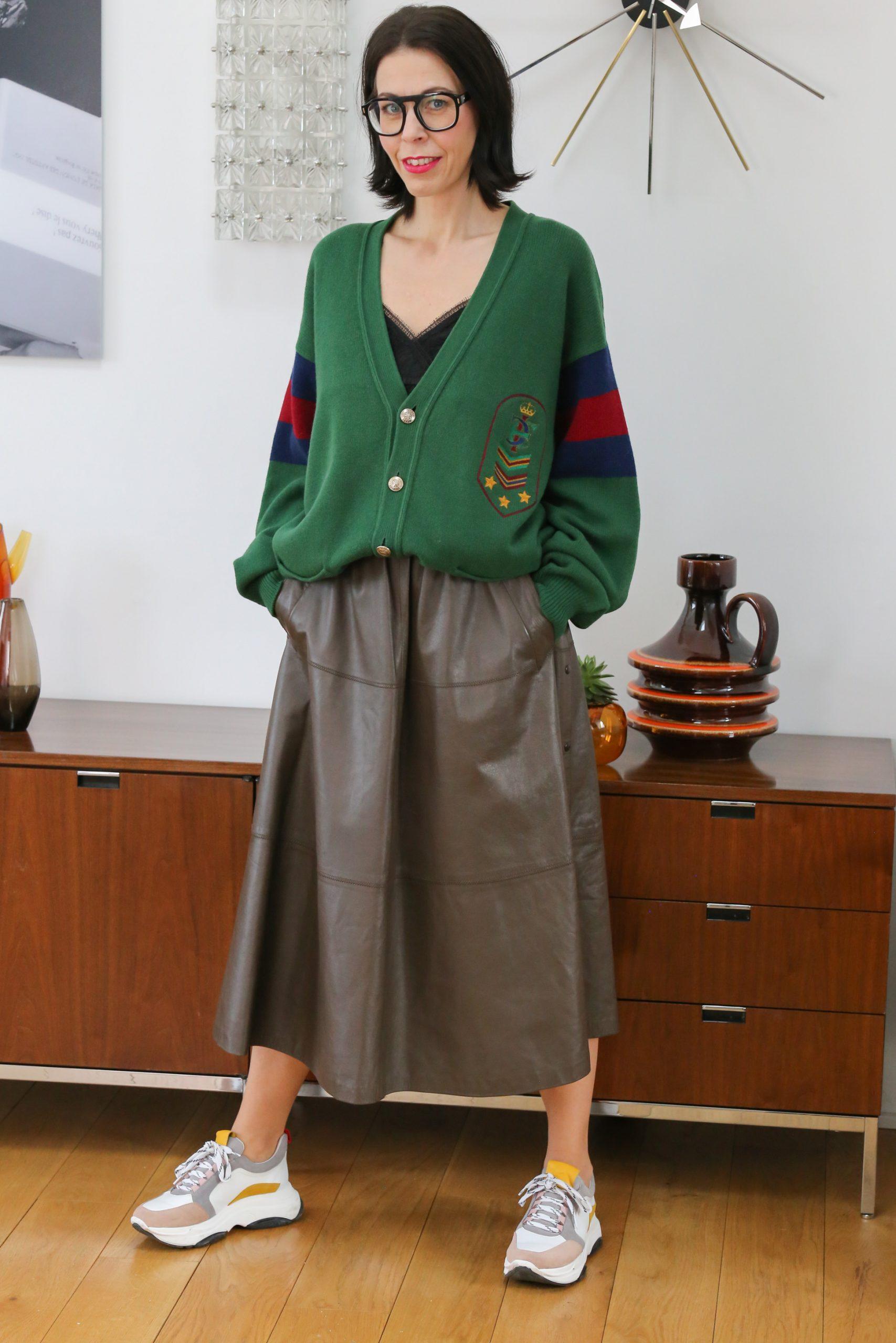Kleiderschrank-Experiment Eine Frau mit schwarzen langen Haaren mit einer grünen Strickjacke und einem braunen Lederrock und Sneaker
