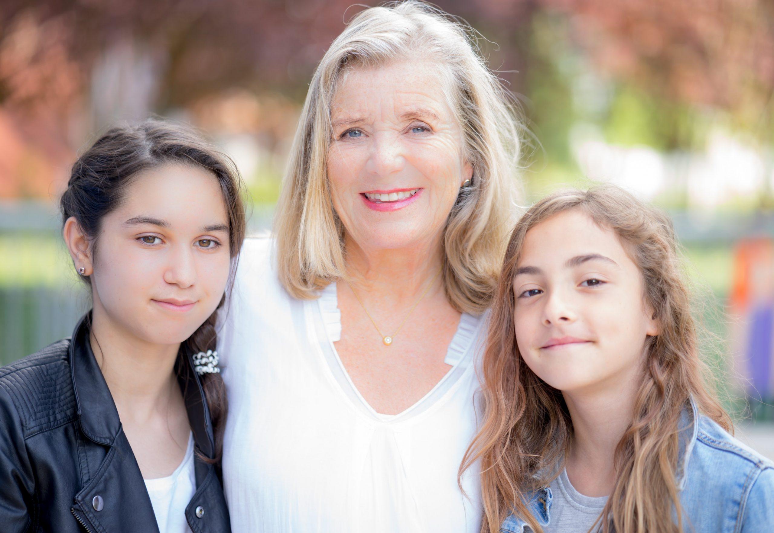 Jutta Speidel mit zwei jungen Mädchen an ihrer Seite in ihrer Stiftung HORIZONT e.V.