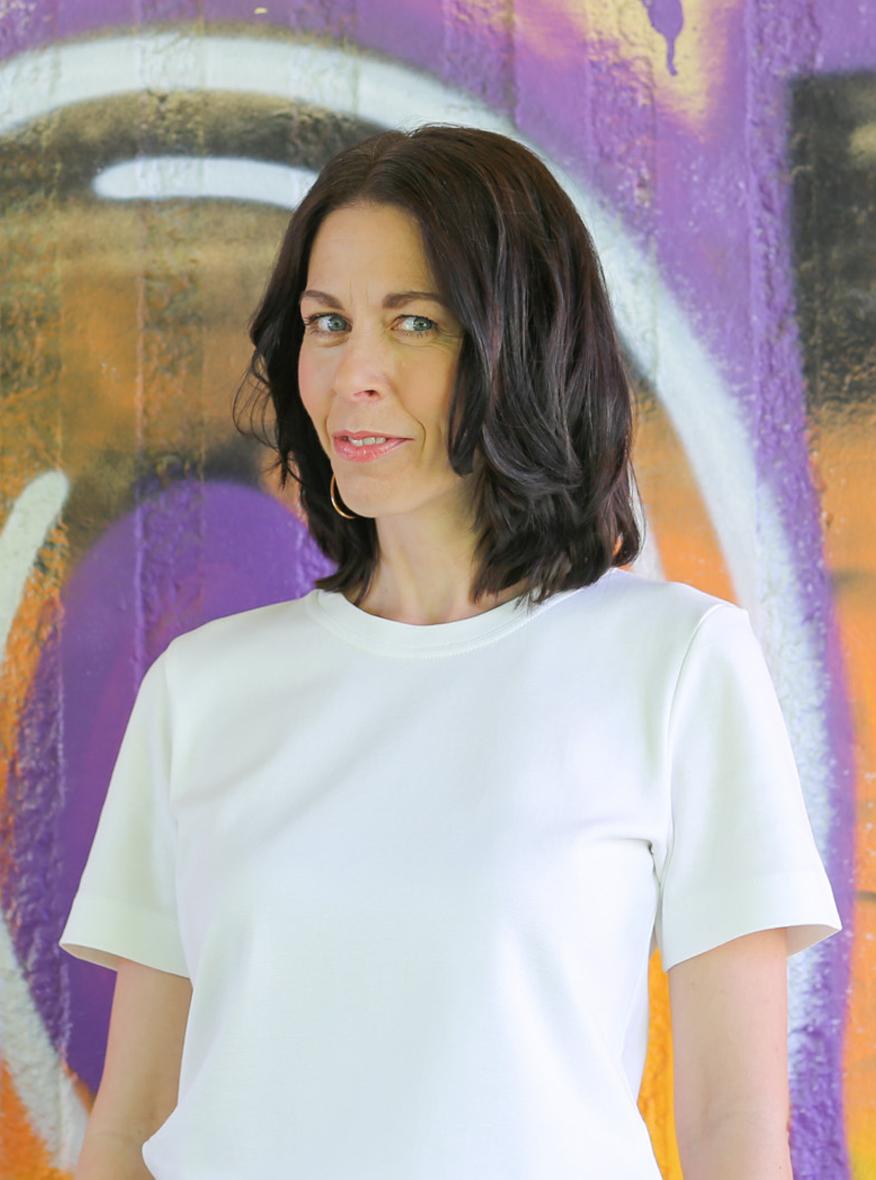 weißes T-Shirt wird von einer Frau mit schwarzen halblangen Haaren und Jeans getragen.