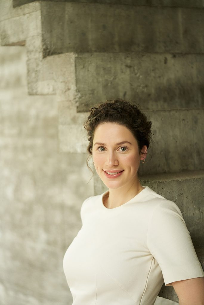 Hanna Greis Eine junge Frau mit lockigem hochgestecktem Haar strahlt in die Kamera